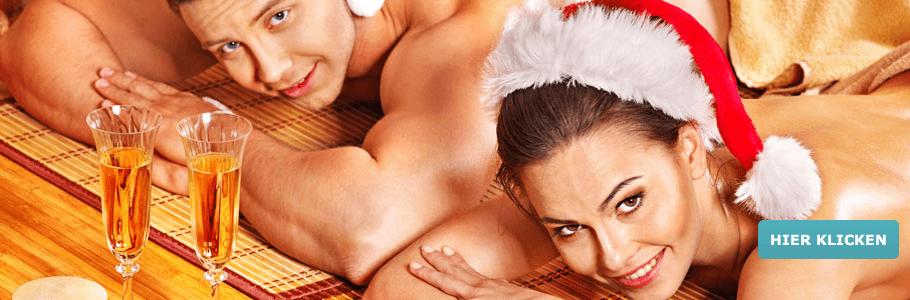 Paar mit Sektgläsern und Weihnachtsmüzen während Wellness